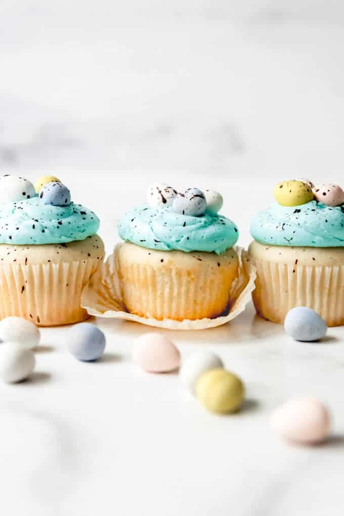 An image of an unwrapped vanilla Easter cupcake with Cadbury mini eggs for decoration.