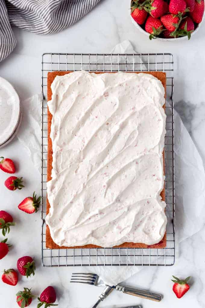 An overhead image of a large strawberries and cream sheet cake with fresh strawberries.