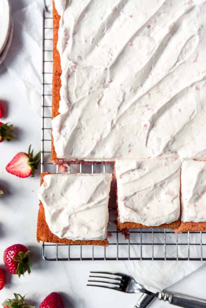 An image of a fresh strawberry sheet cake with whipped cream frosting on a wire rack.
