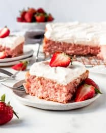 An image of a piece of strawberry cake with whipped cream cream cheese frosting.
