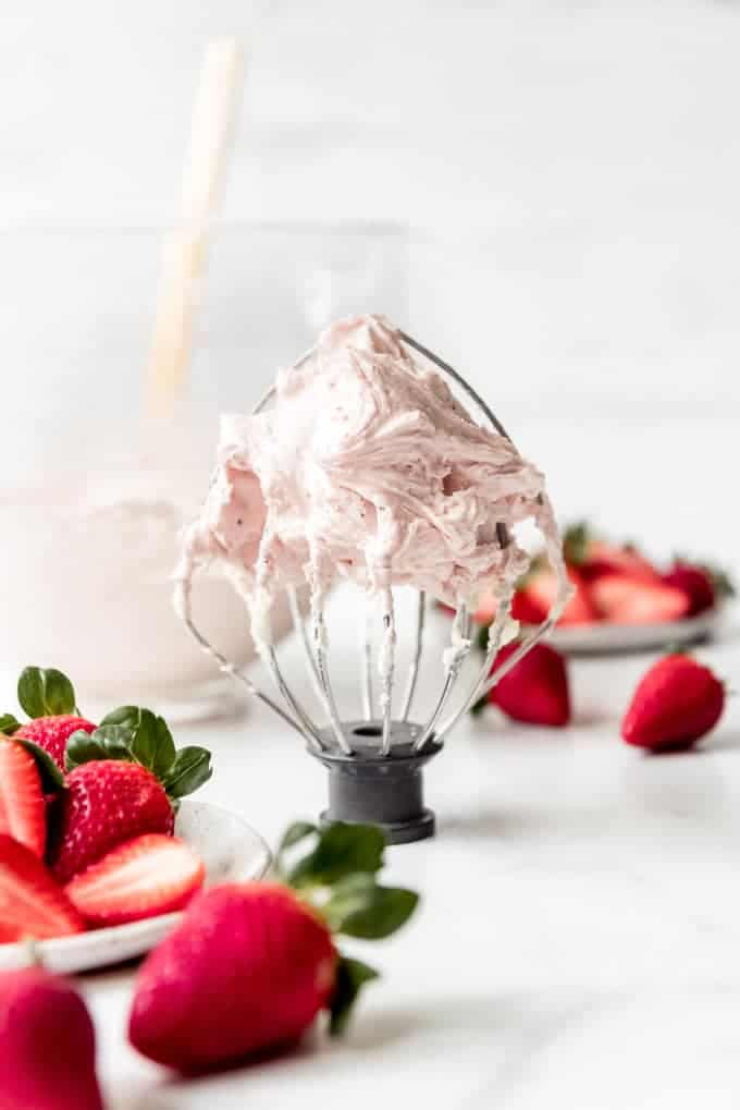 An image of light and fluffy strawberry frosting on a whisk attachment.