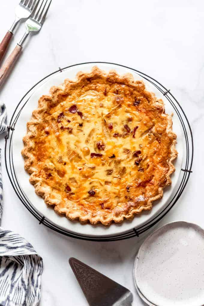 An image of a bacon and cheese quiche on a cooling rack.