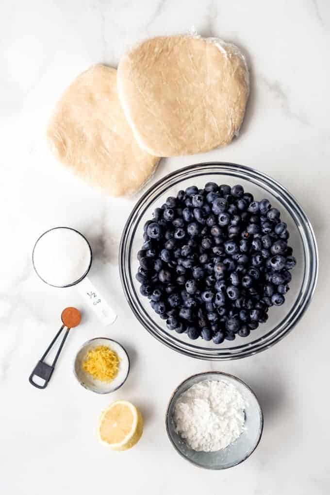 The ingredients for making a homemade blueberry pie recipe.