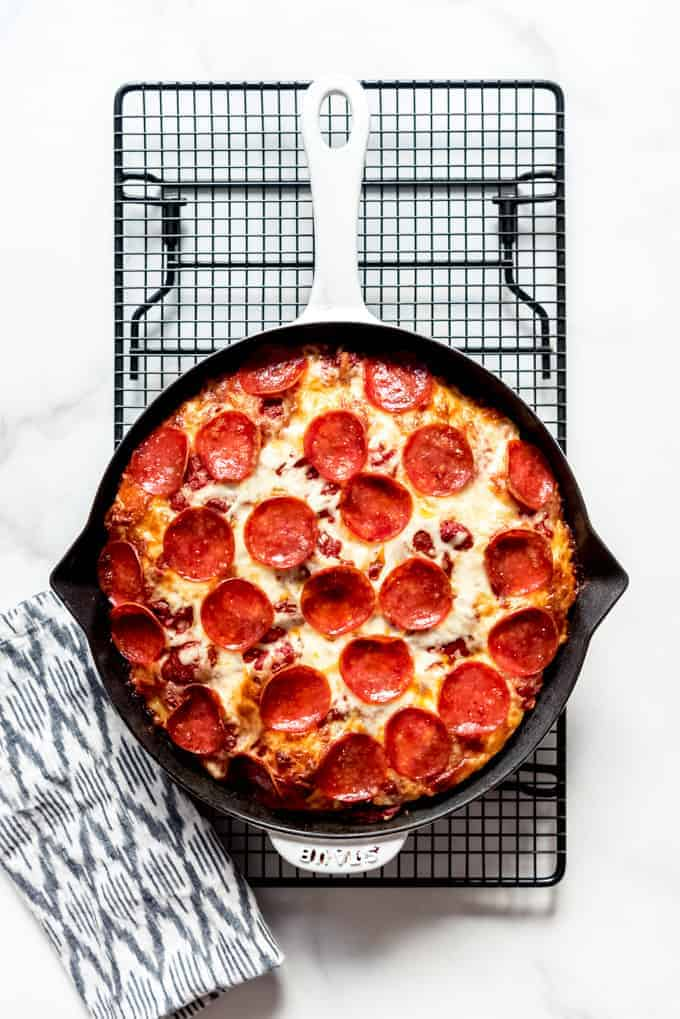 A pepperoni pizza in a cast iron pan on a wire rack.