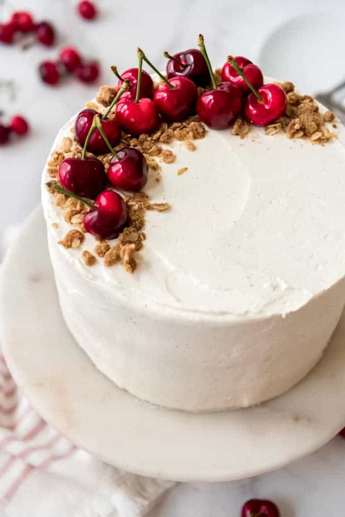 A three layer cake frosted with vanilla bean buttercream and decorated with oat crisp and fresh cherries.