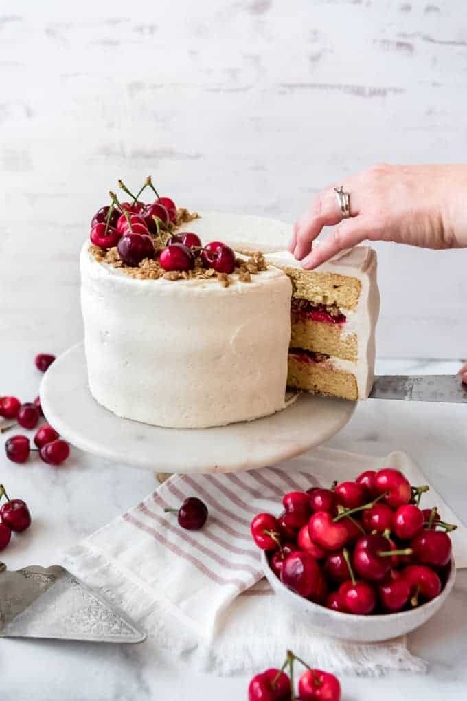 A slice of cherry crisp cake being removed from the rest of the cake next to a bowl of cherries.