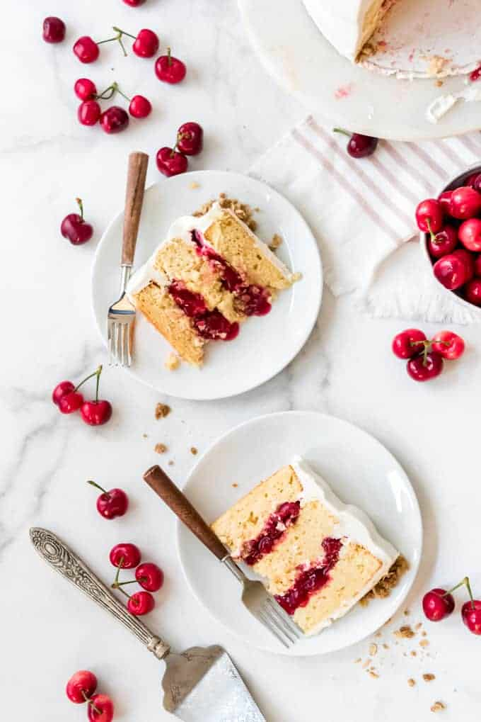 Slices of cherry crisp cake on white plates with forks and fresh cherries scattered around them.