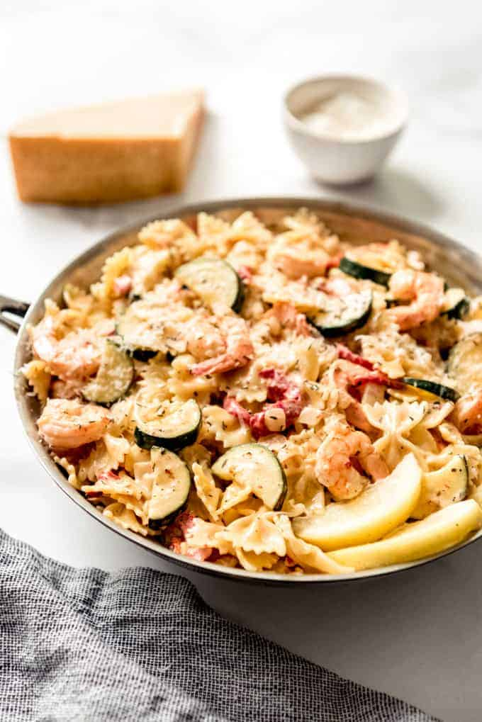 A pan full of shrimp and pasta with vegetables.
