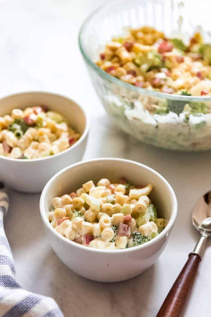 Small white bowls with macaroni salad next to a larger serving bowl.