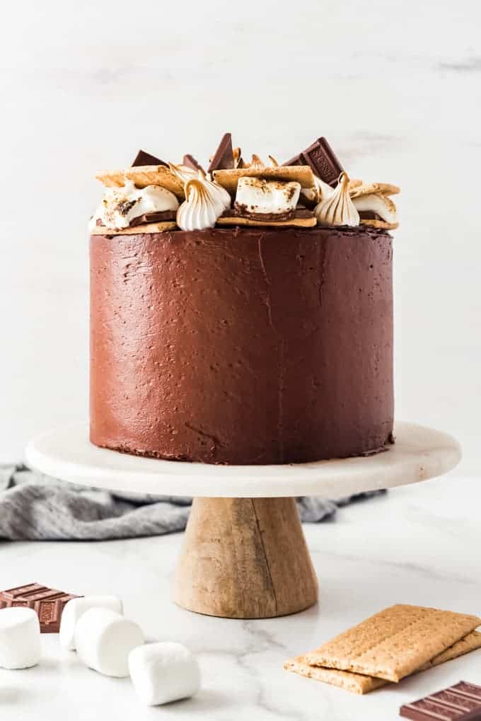 A chocolate s'mores cake on a cake stand.