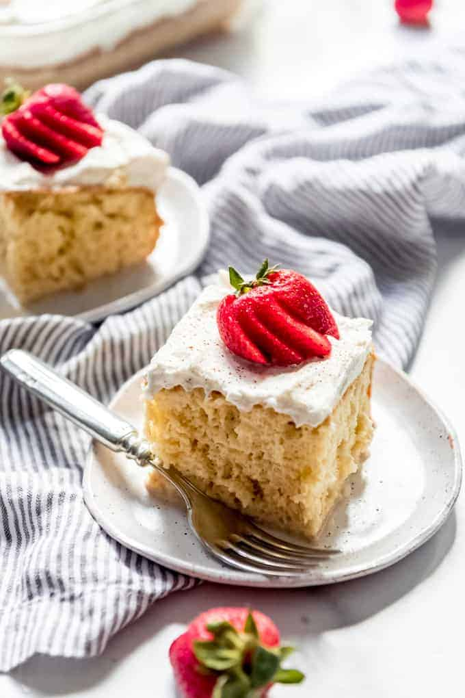 sliced and frosted squares of tres leches cake on plates with fanned strawberries as garnish on top