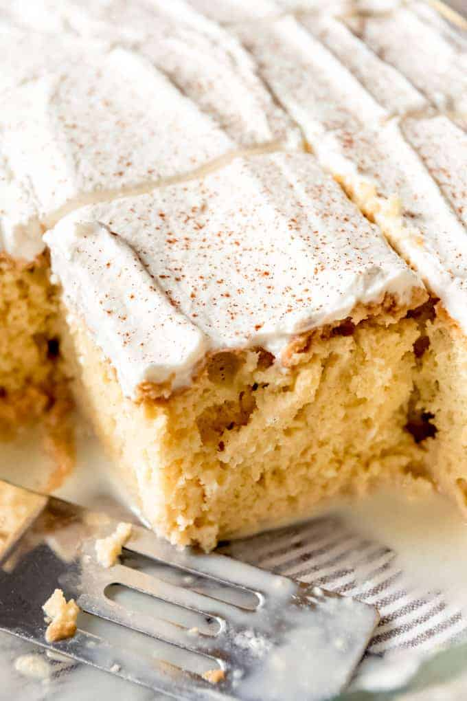 tres leches cake sliced into square serving sized pieces with a fork to the side