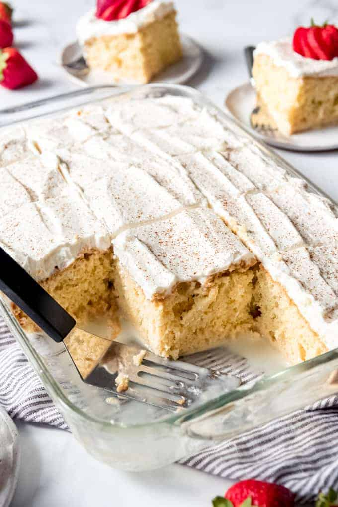 a baking dish with sliced and frosted tres leches cake with some slices removed