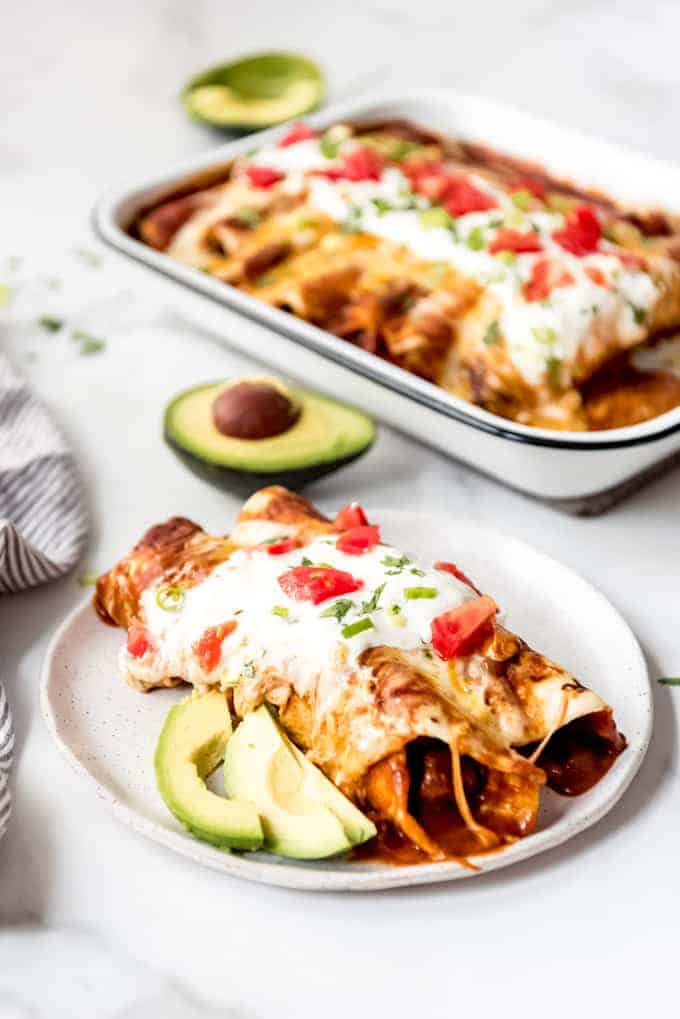 Two beef enchiladas on a white plate with slices of avocado.