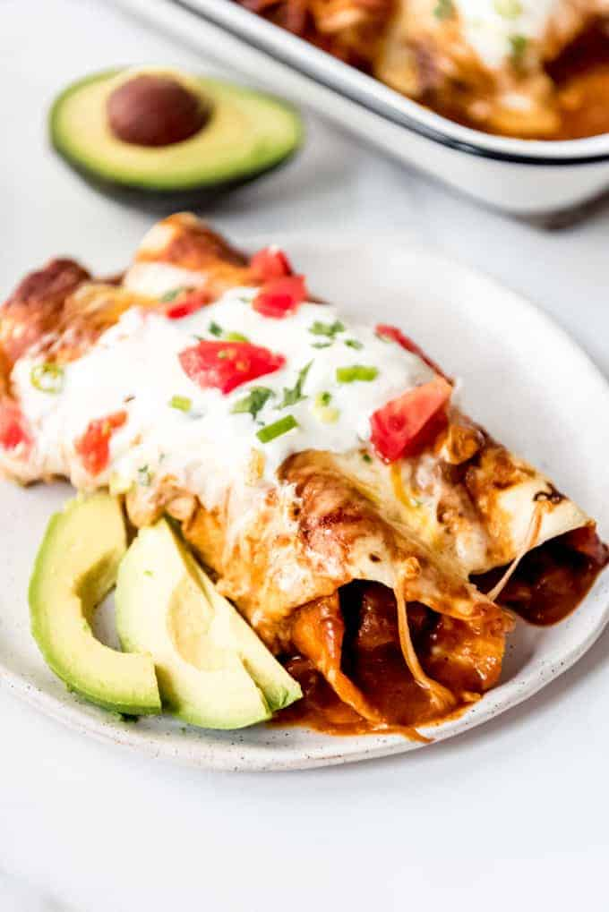 Two beef enchiladas topped with sour cream and tomatoes on a white plate with avocado slices.