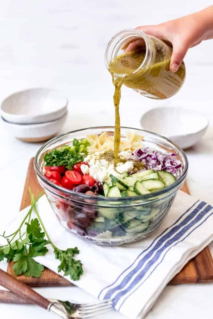 Greek dressing being poured over a bowl filled with ingredients for cold pasta salad.
