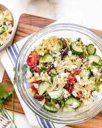 A pasta salad with cucumbers, tomatoes, kalamata olives, and feta cheese.