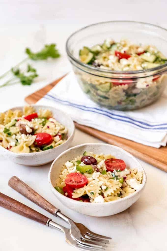 Bowls of Greek pasta salad in front of a larger serving bowl.