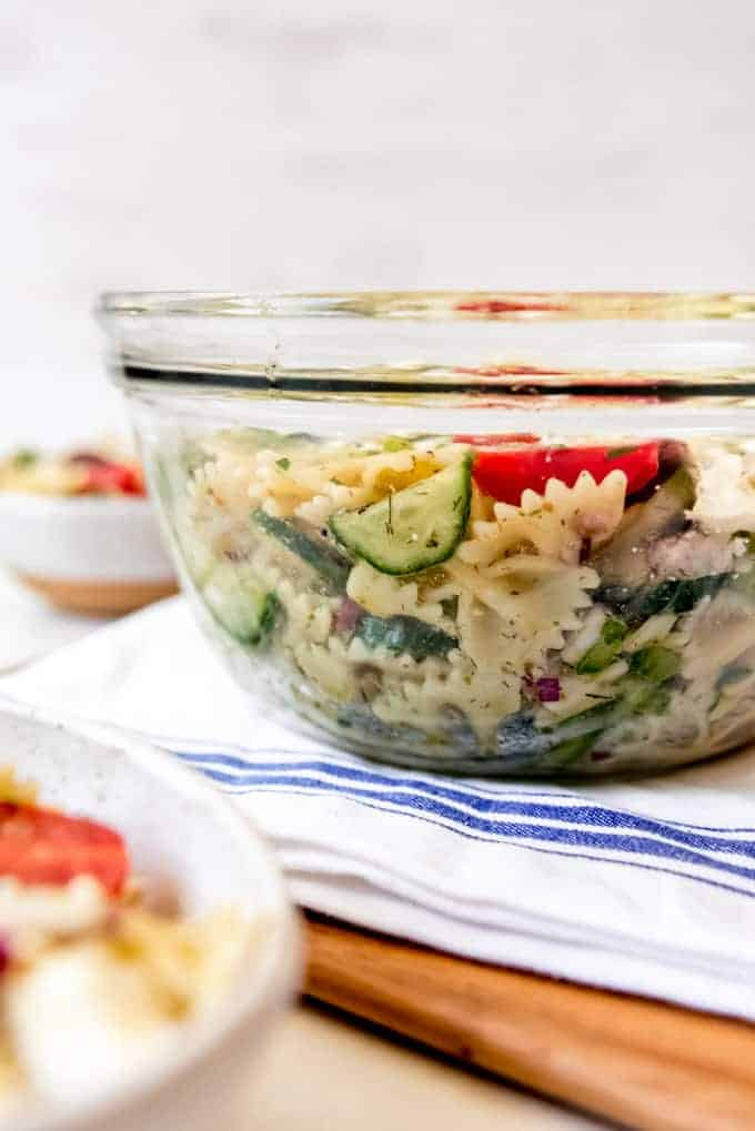 A side view of a glass bowl filled with Greek pasta salad.