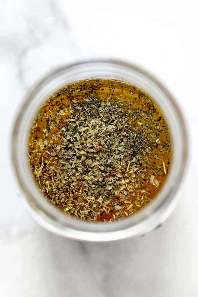 An overhead image of dried herbs in a jar with oil and vinegar for a Greek vinaigrette dressing.