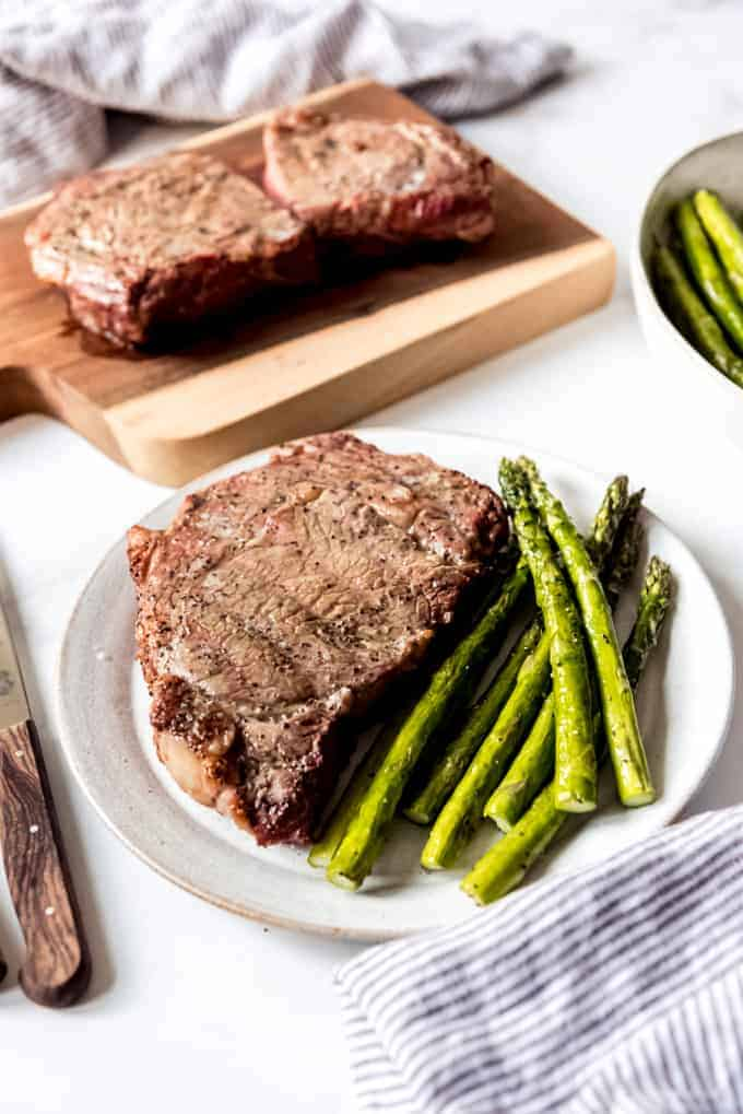 A grilled ribeye steak on a plate with grilled asparagus and another ribeye steak on a cutting board in the background.