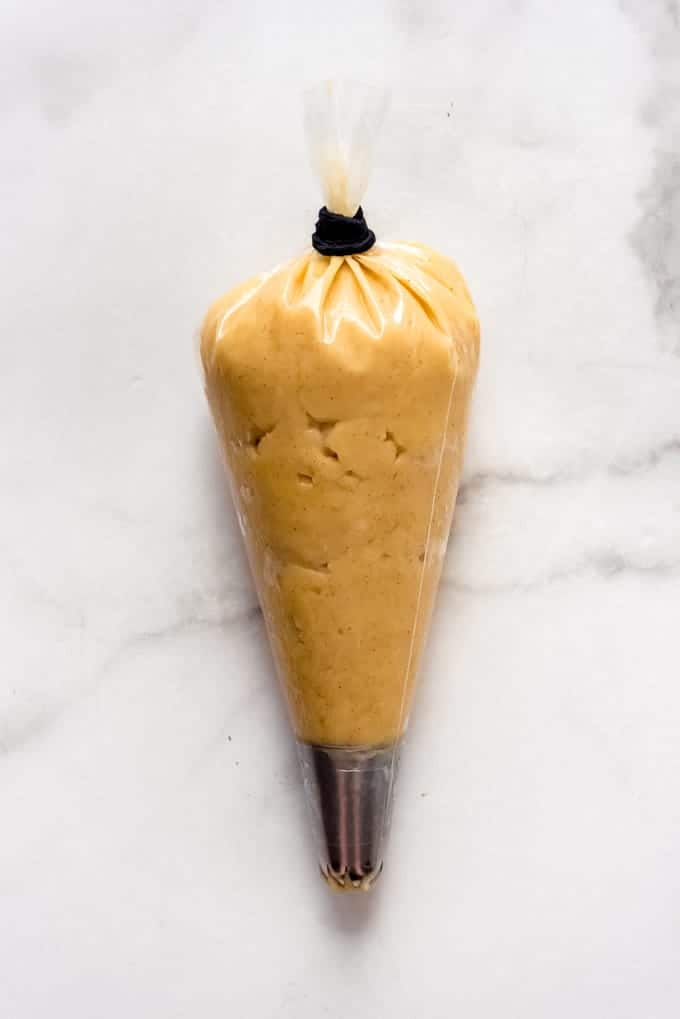 An image of pate a choux churro pastry dough in a pastry bag fitted with a closed star tip.