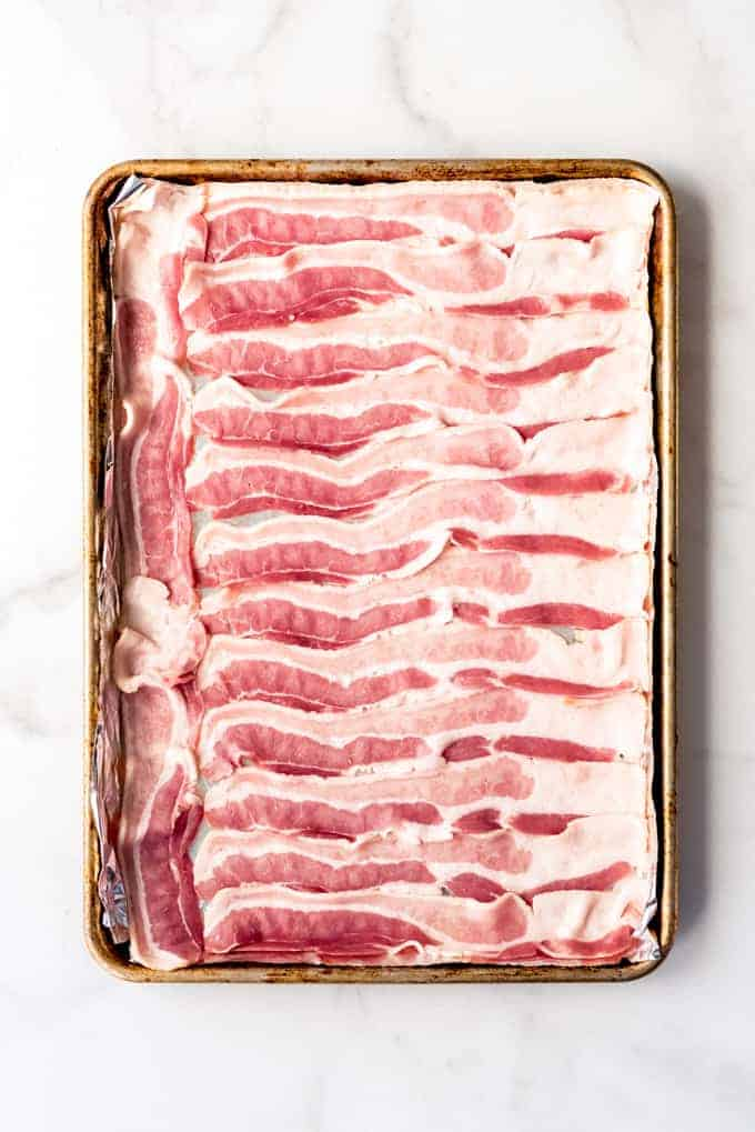 Slices of raw, uncooked bacon on a baking sheet.