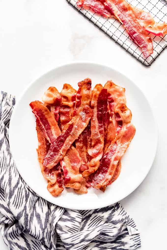 Slices of crispy bacon on a white plate beside a cloth napkin.