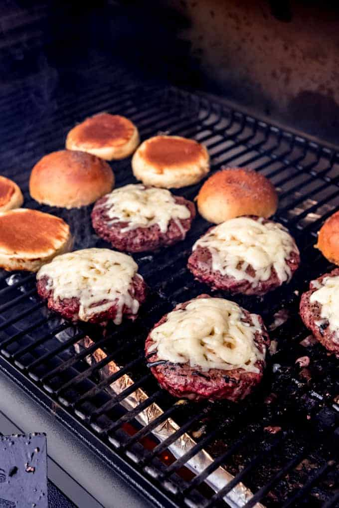 Hamburgers on a grill with cheese melting on top and buns toasting next to them..