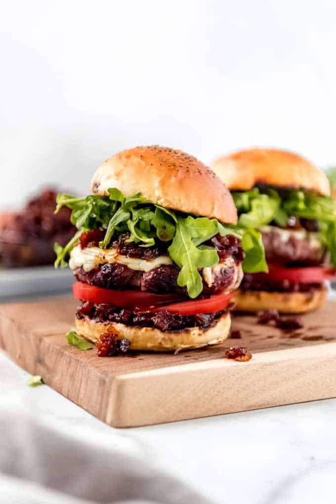 Two hamburgers on a wooden cutting board topped with arugula and bacon jam.