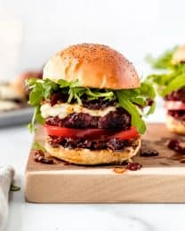 A burger topped with bacon jam, arugula, cheese, and sliced tomatoes on a cutting board.