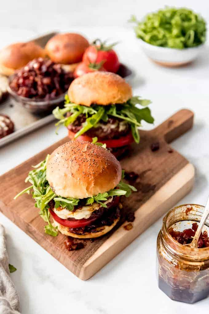 Hamburgers on a wooden cutting board with poppy seed buns and bacon jam.