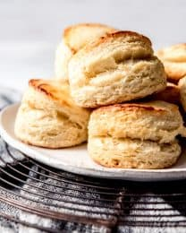 Buttermilk biscuits piled on a plate on a wire cooling rack on a towel