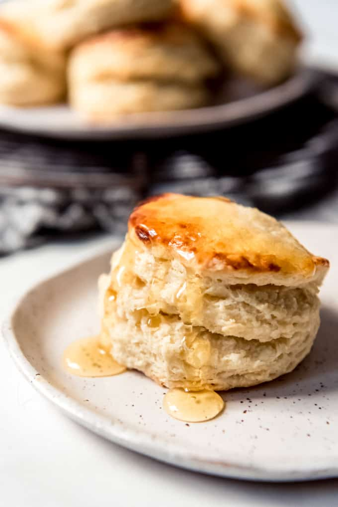A flaky buttermilk biscuit with honey dripping down its sides.