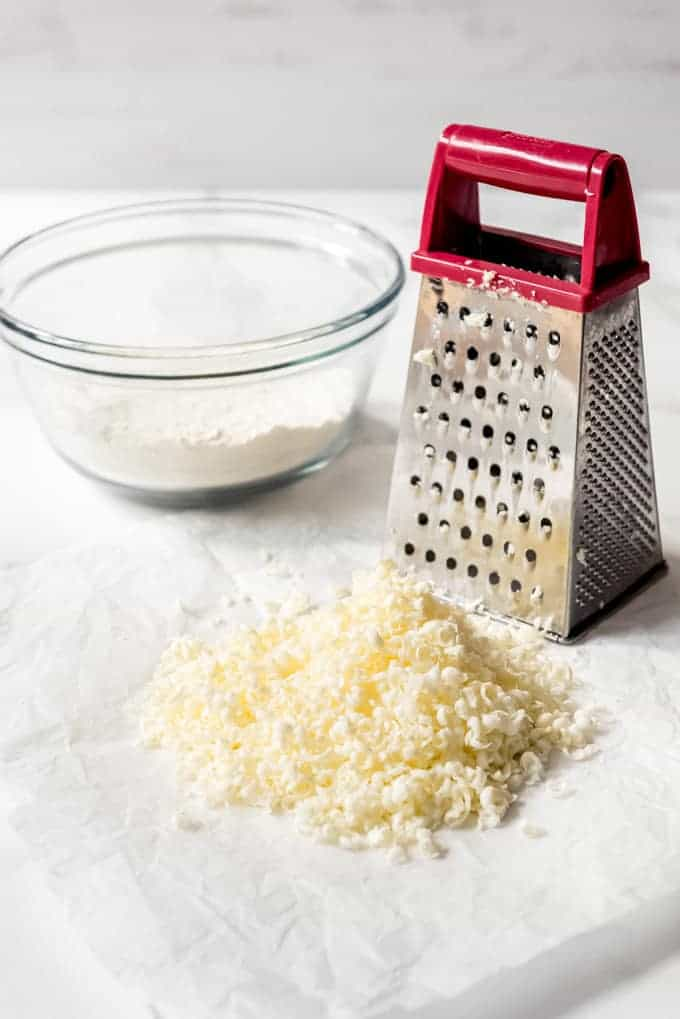 A box grater next to a pile of grated butter in front of a glass bowl filled with flour.