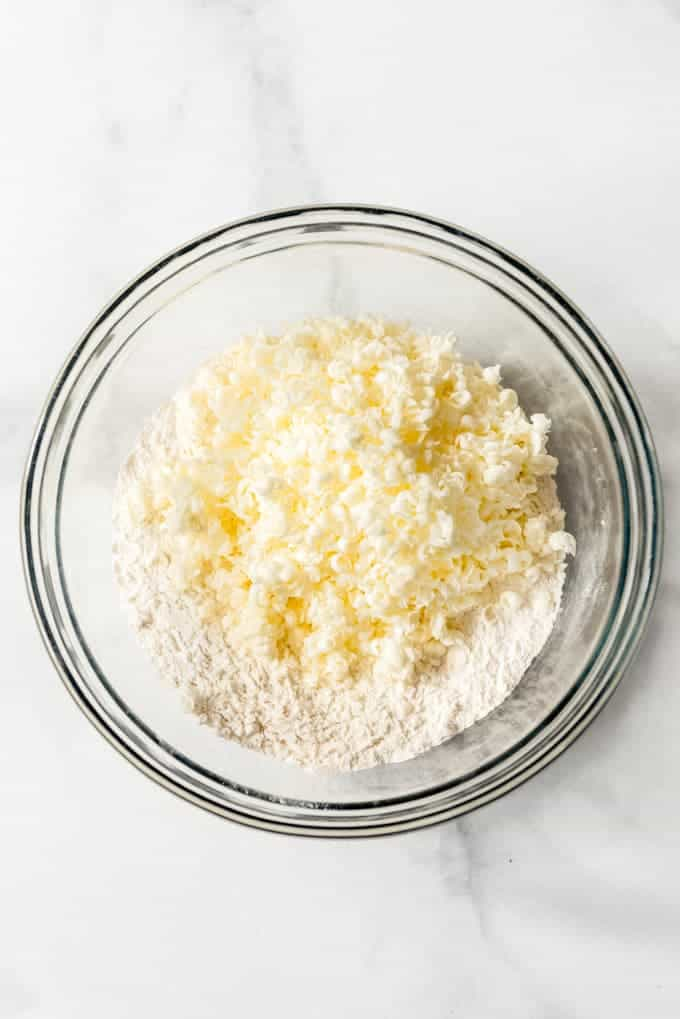 grated butter in a bowl of flour and dry ingredients to make homemade biscuits