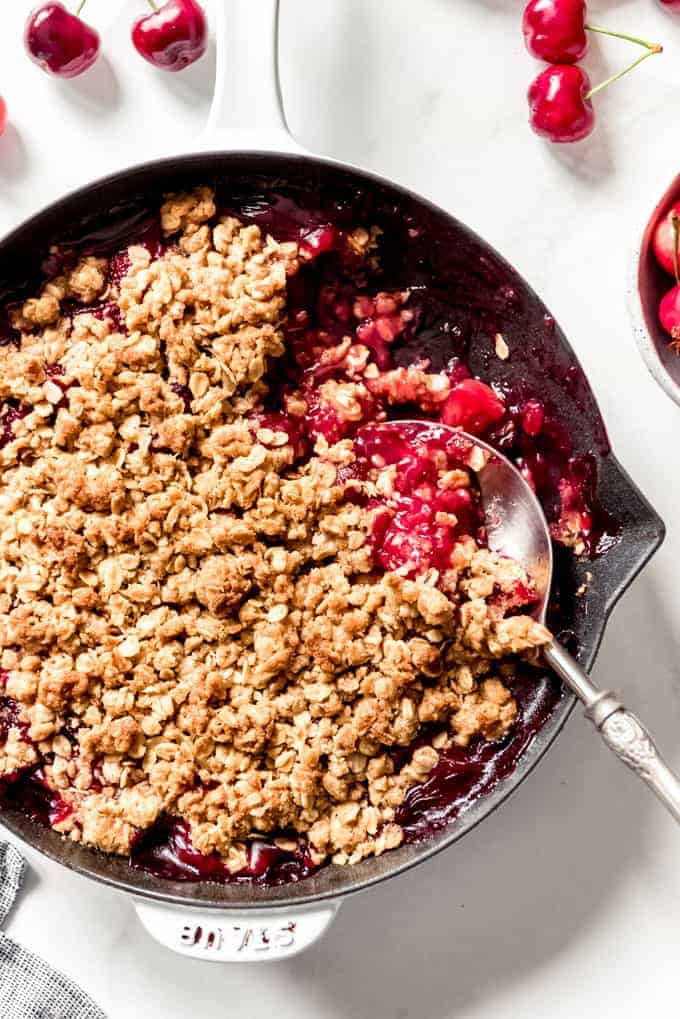 A serving spoon scooping out a portion of cherry crisp from a cast iron skillet.
