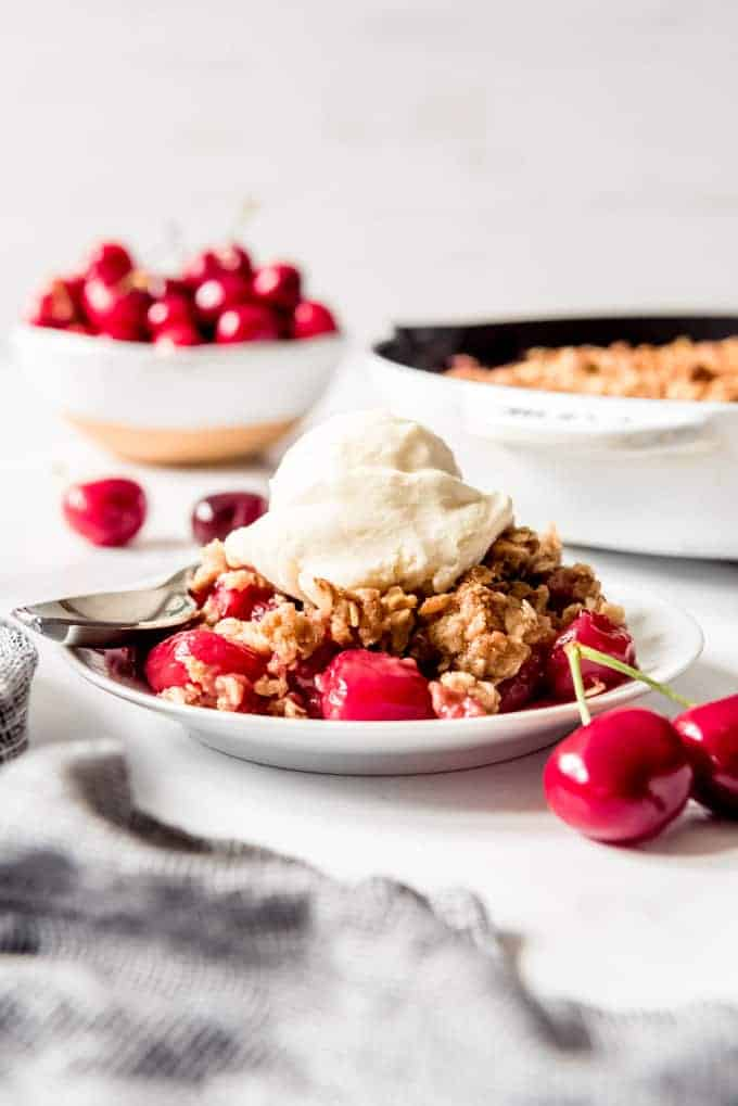 A serving of cherry crisp topped with vanilla ice cream on a white plate.