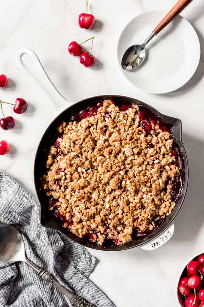 A large cast iron skillet with crisp oat topping over cherry pie filling next to some fresh cherries and a white plate.