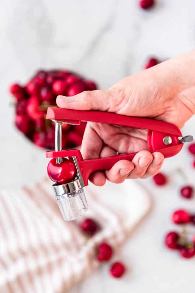 A hand holding a cherry pitter to remove the pit from a cherry.