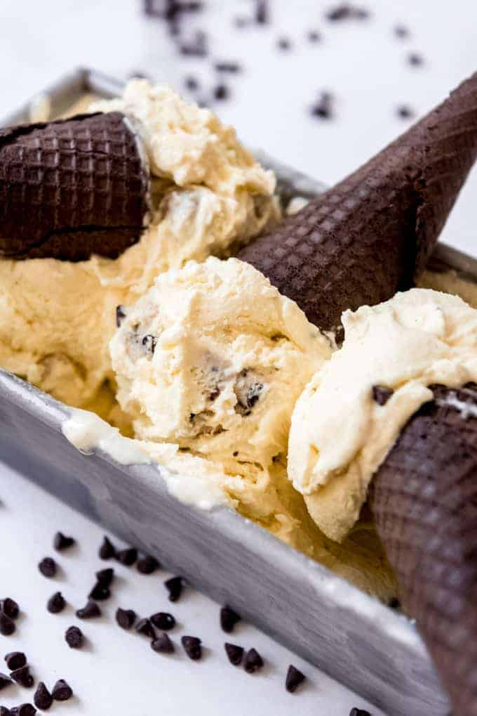 Scoops of cookie dough ice cream with chocolate Oreo sugar cones in a bread pan.
