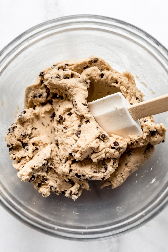 A glass bowl with a white spatula mixing mini chocolate chips into cookie dough.