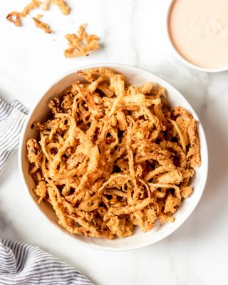 A white bowl filled with crispy fried onion strings.