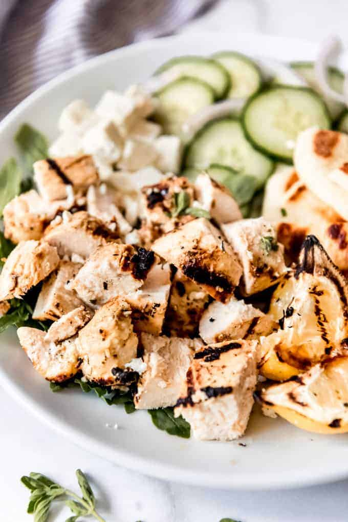 Bite-size pieces of grilled marinated chicken on a white plate.