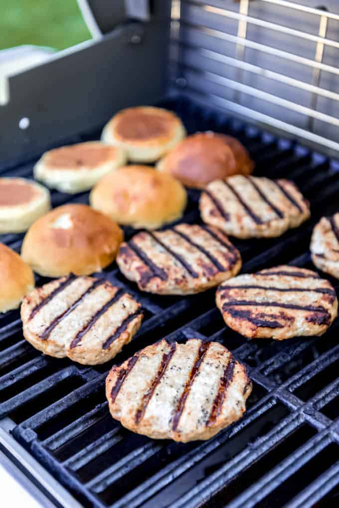 Turkey burgers on a gas grill with buns toasting next to them..