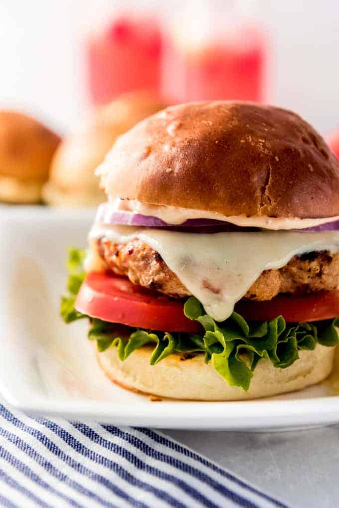 A turkey burger on a bun with melted cheese, tomato, green leaf lettuce, and red onion.