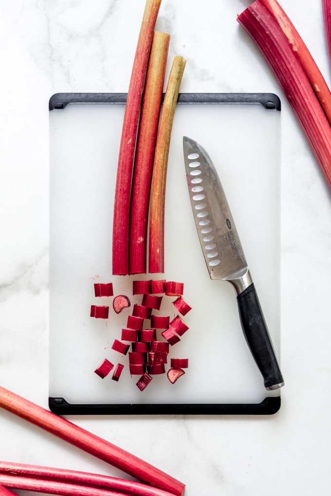 Rhubarb stalks on a cutting board being chopped into 1-inch pieces with a knife.