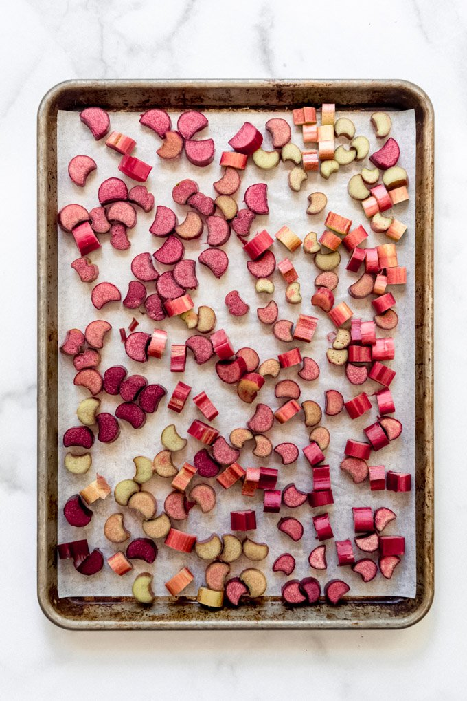 A baking sheet lined with parchment paper covered in a single layer of chopped rhubarb.