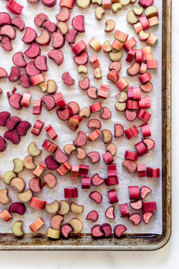 Rhubarb stalks sliced into 1-inch pieces on a baking sheet lined with parchment paper.