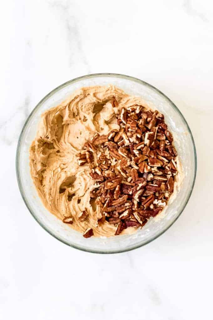 A glass mixing bowl full of blondie batter and chopped pecans.